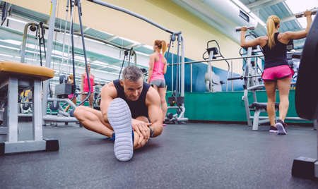 Handsome man stretching in a fitness center and two beautiful women doing exercises with dumbbells in the background photo