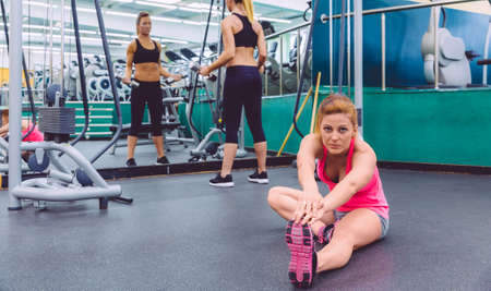 Beautiful woman stretching in a fitness center and female friend doing exercises with dumbbells in the background photo