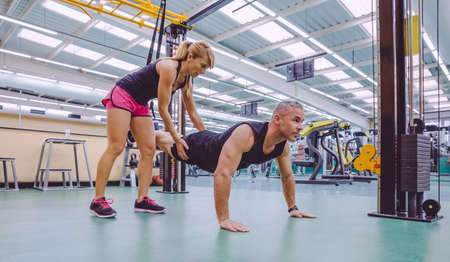 Female personal trainer teaching to man in a hard suspension training with fitness straps on a fitness center