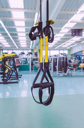 Closeup of fitness straps ready to use in a fitness center. Suspension training concept. Stock Photo