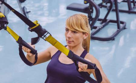 Chân dung người phụ nữ xinh đẹp làm đào tạo hệ thống treo cứng với dây đai tập thể dục tại một trung tâm thể dục thẩm mỹ. Sức khỏe và thể thao khái niệm lối sống.