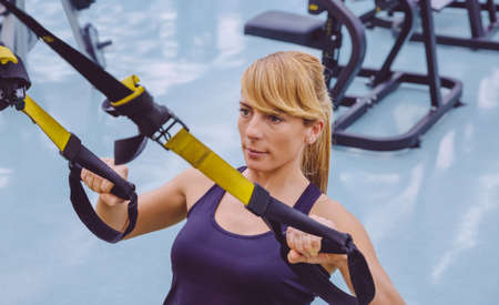 Portrait of beautiful woman doing hard suspension training with fitness straps in a fitness center. Healthy and sporty lifestyle concept.