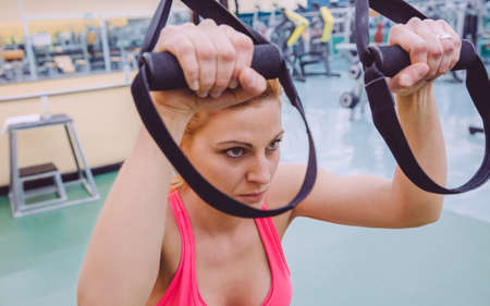 Closeup of beautiful woman doing hard suspension training with fitness straps in a fitness center. Healthy and sporty lifestyle concept.