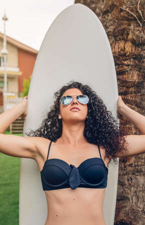 Closeup of curly brunette surfer woman with black bikini and sunglasses standing out in front of her surfboard photo