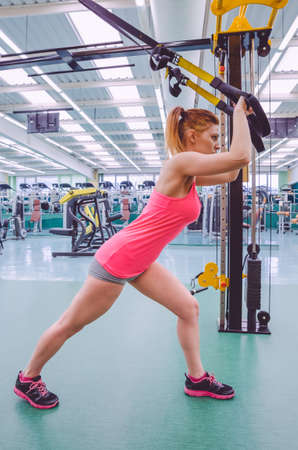 circuit: Beautiful woman doing hard suspension training with fitness straps in a fitness center. Healthy and sporty lifestyle concept.