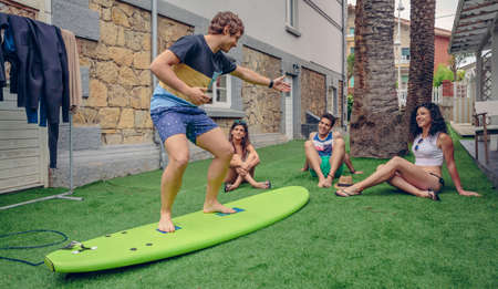 four classes: Group of young people having fun in a summer surf class outdoors. Holidays leisure concept.