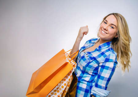 blue plaid: Portrait of happy girl teenager with blue plaid shirt holding shopping bags. Young consumer concept. Stock Photo