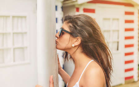 Closeup of beautiful young surfer woman with white top and sunglasses kissing her lovely surfboard photo