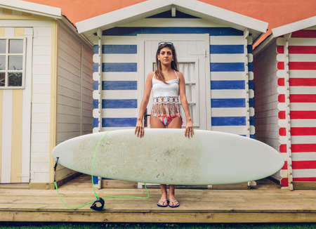 Portrait of beautiful young surfer woman with white top and bikini holding surfboard over a beach striped huts background. Summer leisure concept. photo