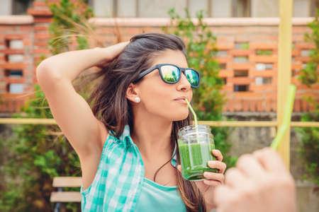 Bella giovane donna con gli occhiali da sole che beve frullato di verdure verdi con paglia in un giorno d'estate all'aperto. Sano bevande biologiche concetto.