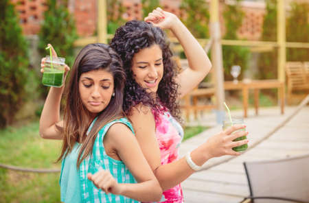 summer fruit: Young happy women couple with green vegetable smoothies dancing and having fun in a summer party outdoors. Young people lifestyle concept.
