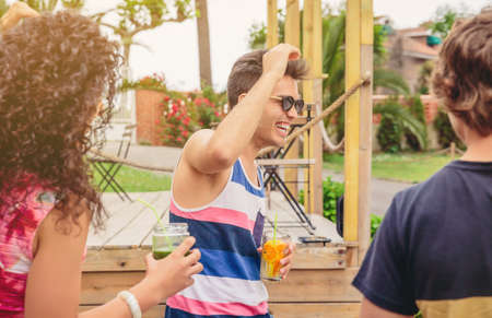 four people: Group of young happy people with healthy drinks having fun in a summer party outdoors. Young people lifestyle concept.