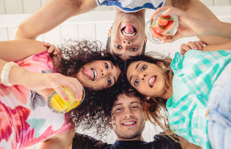 summer fruit: Below view of young happy people with their heads together and holding healthy drinks having fun in a summer party. Young people lifestyle concept.