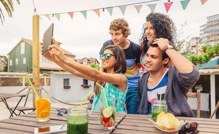fiestas electronicas: Grupo de jóvenes felices teniendo una selfie con una tableta electrónica en una fiesta de verano al aire libre. Los jóvenes estilo de vida concepto. Foto de archivo
