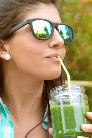 organic drinks: Beautiful young woman with sunglasses drinking green vegetable smoothie with straw in a summer day outdoors. Healthy organic drinks concept.