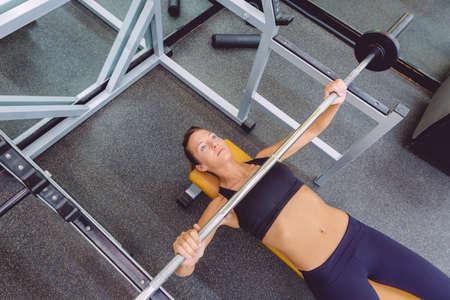 capacitaci�n: Hermosa mujer haciendo ejercicios con barra en un entrenamiento de press de banca en un centro de fitness Foto de archivo