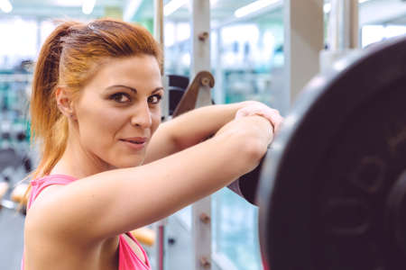 Beautiful sporty woman smiling and resting over barbell after a muscular training in fitness center