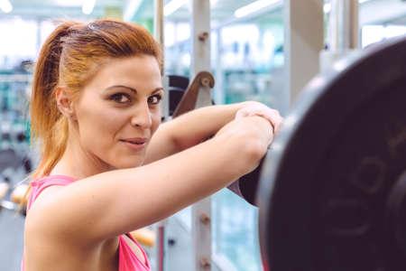 gimnasio mujeres: Mujer deportiva hermosa sonriendo y descansando sobre barra después de un entrenamiento muscular en el gimnasio