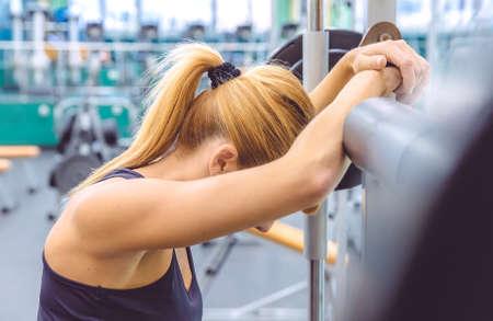 Mooie sportieve vrouw rusten moe na het opheffen barbell op een gespierde training in het fitnesscentrum