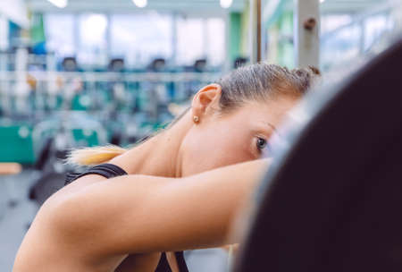 fitness training: Beautiful sporty woman resting tired after lifting barbell on a muscular training in fitness center Stock Photo