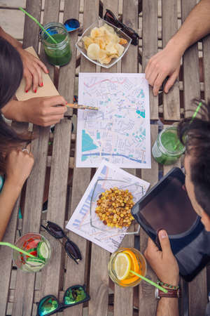 healthy looking: Top view of young tourist friends looking maps in a break travel over a wooden table with healthy drinks and snacks. Holidays and tourism concept