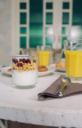 glass table: Closeup of yogurt with granola and berries in a glass over table served with orange juice and homemade cookies for a delicious and healthy breakfast