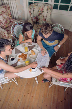 healthy looking: Top view of young tourist friends looking maps and enjoying a healthy breakfast in the morning. Holidays and tourism concept. Stock Photo