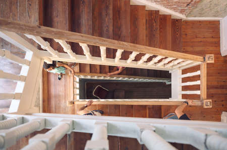 banister: Top view of people hands holding a wooden banister and climbing home staircase