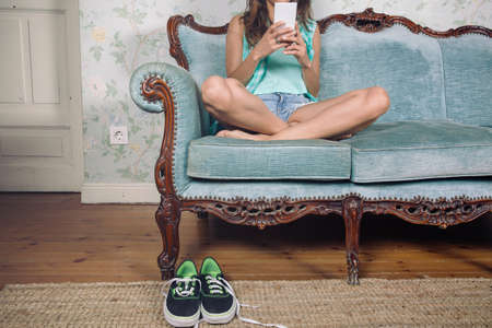 sofa furniture: Closeup of beautiful young woman looking smartphone sitting on a classic sofa with legs crossed and her sneakers over the carpet