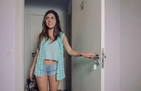 格子縞のシャツと短いジーンズのスーツケースとホテルの部屋のドアを開けると若い女性 写真素材