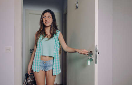 Young woman with plaid shirt and short jeans holding a suitcase and opening door of hotel room