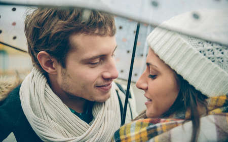 Closeup of young beautiful couple looking at each other with love under the umbrella in an autumn rainy day. Love and couple relationships concept.