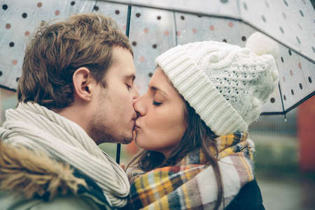 couple winter: Closeup of young beautiful couple kissing under the umbrella in an autumn rainy day. Image focused on the lips.