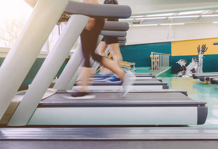 fitness training: Closeup of people legs in motion during a treadmill training session on fitness center