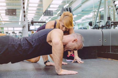 encouraging: Woman personal trainer encouraging to muscle man during a hard push ups training day on fitness center