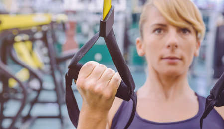 circuit: Closeup of fitness strap in the hand of woman doing hard suspension training in a fitness center. Healthy and sporty lifestyle concept. Stock Photo