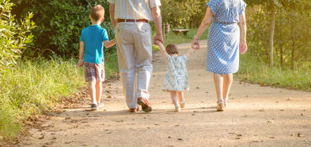 Closeup of grandparents and grandchildren walking on a nature path