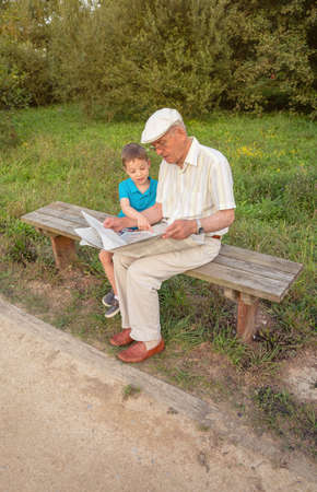 two generations: Senior man reading newspaper and cute child pointing an article with his finger sitting on park bench. Two different generations concept.