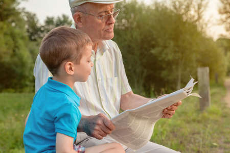 Closeup of senior man and cute child reading a newspaper sitting over a nature background. Two different generations concept. Stock Photo
