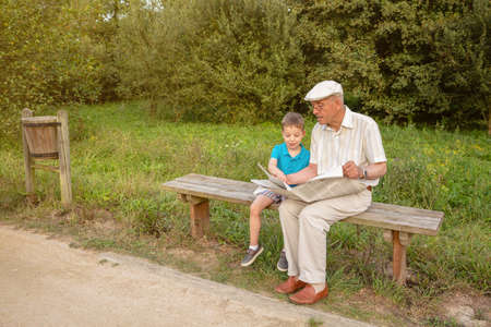 two generations: Senior man and cute child reading a newspaper sitting on park bench. Two different generations concept. Stock Photo