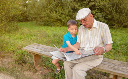 Senior man reading newspaper and cute child pointing an article with his finger sitting on park bench. Two different generations concept.