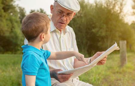 그의 손가락이 자연 배경 위에 앉아 기사를 가리키는 수석 남자 읽기 신문과 귀여운 아이의 근접 촬영입니다. 두 개의 서로 다른 세대 개념입니다.