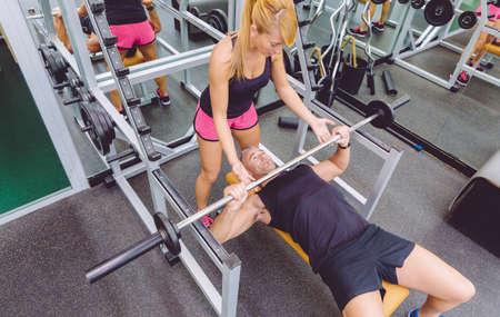 aide à la personne: Femme entraîneur personnel aidant à l'homme de muscle pour un banc d'entraînement de presse correcte avec barre sur un centre de fitness