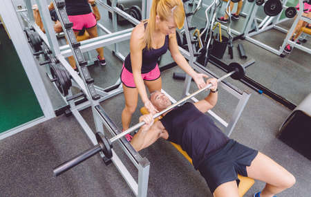 personal trainer: Woman personal trainer helping to muscle man for a correct bench press training with barbell on fitness center Stock Photo