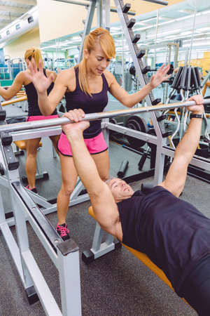 motivating: Woman personal trainer encouraging to muscle man in a bench press training with barbell on fitness center. Motivation in training concept. Stock Photo