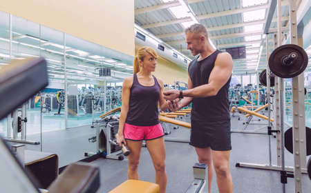 Man personal trainer helping to beautiful woman for a correct training with dumbbells on fitness center Stock Photo