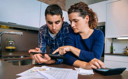 Serious young couple reviewing their bank accounts with a digital tablet and calculator at home. Financial family concept.