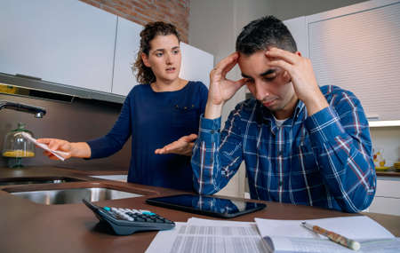 Desesperate young couple with many debts reviewing their bills. Financial family problems concept.