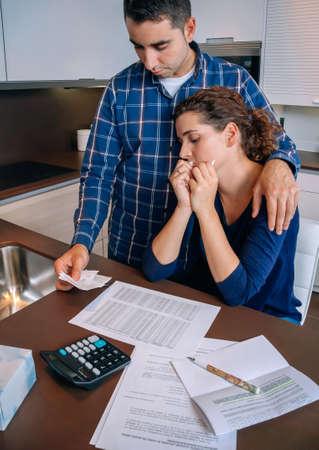 problemas familiares: Marido desempleado joven da consuelo a su esposa desesperada llorando por sus deudas. Concepto financiero de los problemas familiares.