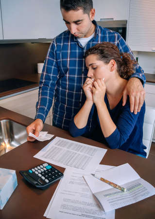 problem: Young unemployed husband gives solace to his desperate wife crying by their debts. Financial family problems concept. Stock Photo
